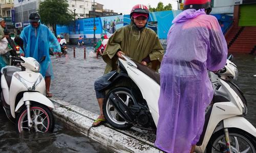 西贡路被深深地淹没,人们在中间地区骑摩托车