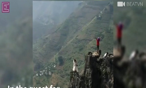 Bride stands on verge of cliff with no protection for pre-wedding shots