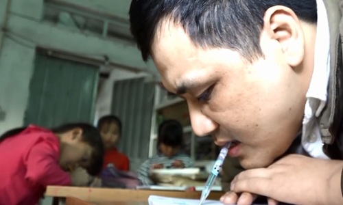 Disabled teacher masters the art of calligraphy... with his mouth