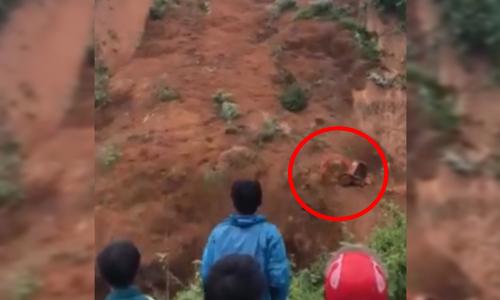 Horrifying moment when landslide sweeps two excavators off the road