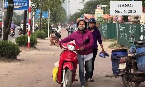 Hanoians walk motorbikes on sidewalk to avoid rush hour traffic