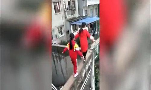 Ba bé gái đi chênh vênh trên bức tường cao 20m