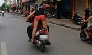 Cô gái vừa đứng lái xe máy vừa hôn bạn trai