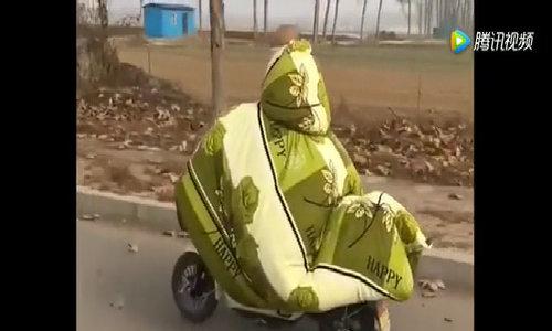 Trùm kín chăn đi xe máy vì lạnh