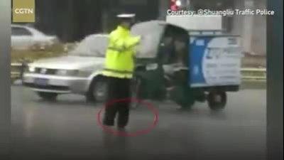 Cảnh sát đi chân đất điều khiển giao thông dưới trời mưa