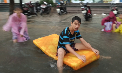 Trẻ con, người lớn bơi thuyền trên phố trong mưa lớn