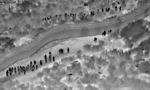 Người di cư đi bộ quanh tường biên giới vào Mỹ