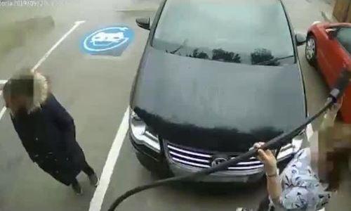Hai phụ nữ lấy sạc ôtô điện để bơm lốp xe
