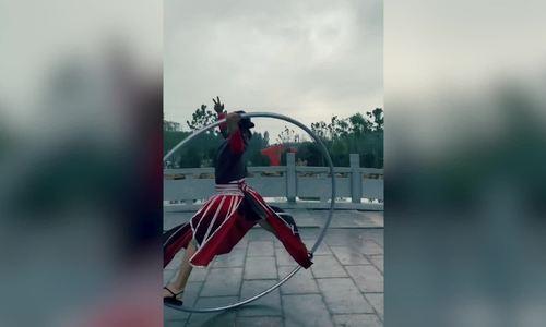 Chàng trai Trung Quốc mặc đồ cổ trang múa vòng thép khổng lồ