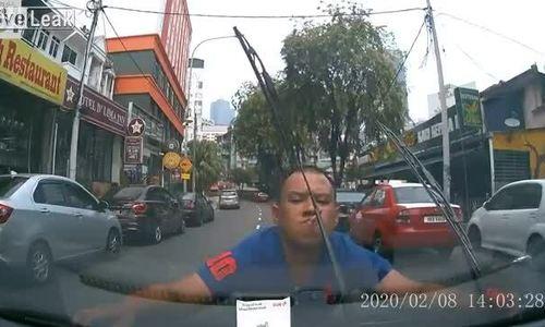 Người đàn ông ôm chặt lấy đầu ôtô